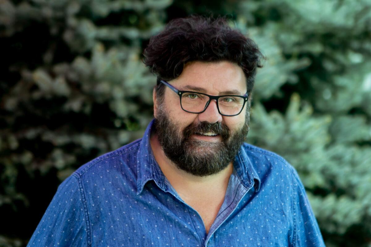 Zdjęcie przedstawia mężczyznę. Ma ciemną brodę, kręcone włosy, na nosie okulary
