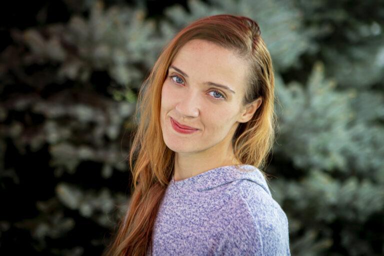 Zdjęcie przedstawia młodą kobietę, uśmiecha się, ma długie włosy