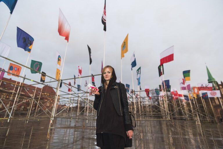 Zdjęcie przedstawia młodą dziewczyną. Za nią na wysokich masztach łopoczą różne flagi.