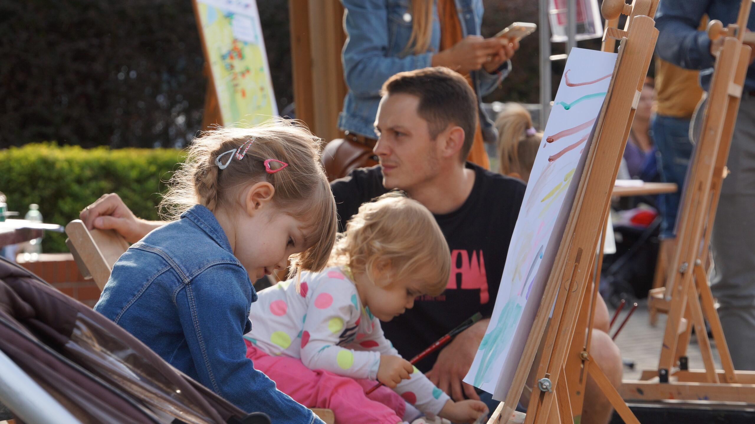 Zdjęcie przedstawia dzieci malujące na sztalugach. Sztalugi ustawione są na świeżym powietrzu.