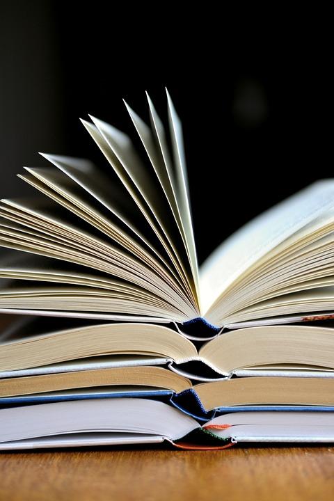 Zdjęcie przedstawia otwarte książki ułożone jedna na drugiej. Są 4 książki.