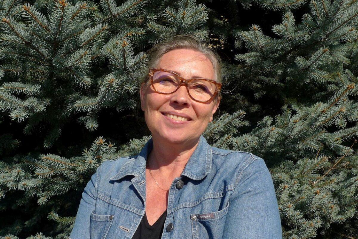 Kobieta w średnim wieku, uśmiecha się, na nosie ma okulary