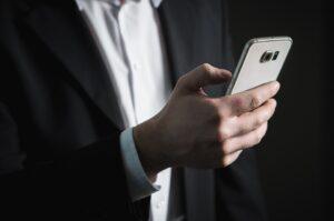 Zdjęcie przedstawia dłoń trzymającą w ręku telefon komórkowy.