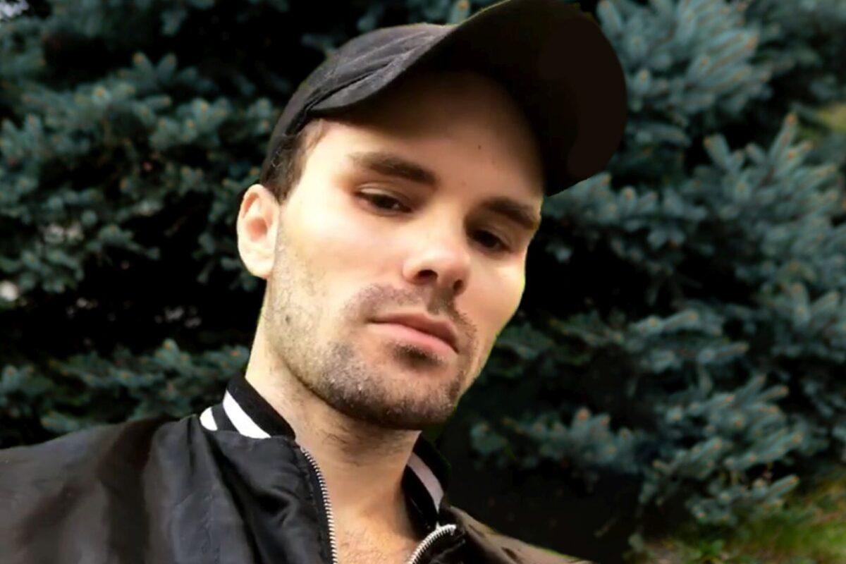 Młody mężczyzna w czapce z daszkiem, Za nim widoczne jest drzewko choinki