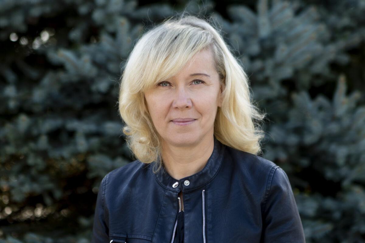 Zdjęcie przedstawia kobietę, ma włosy poniżej ramion z grzywką.