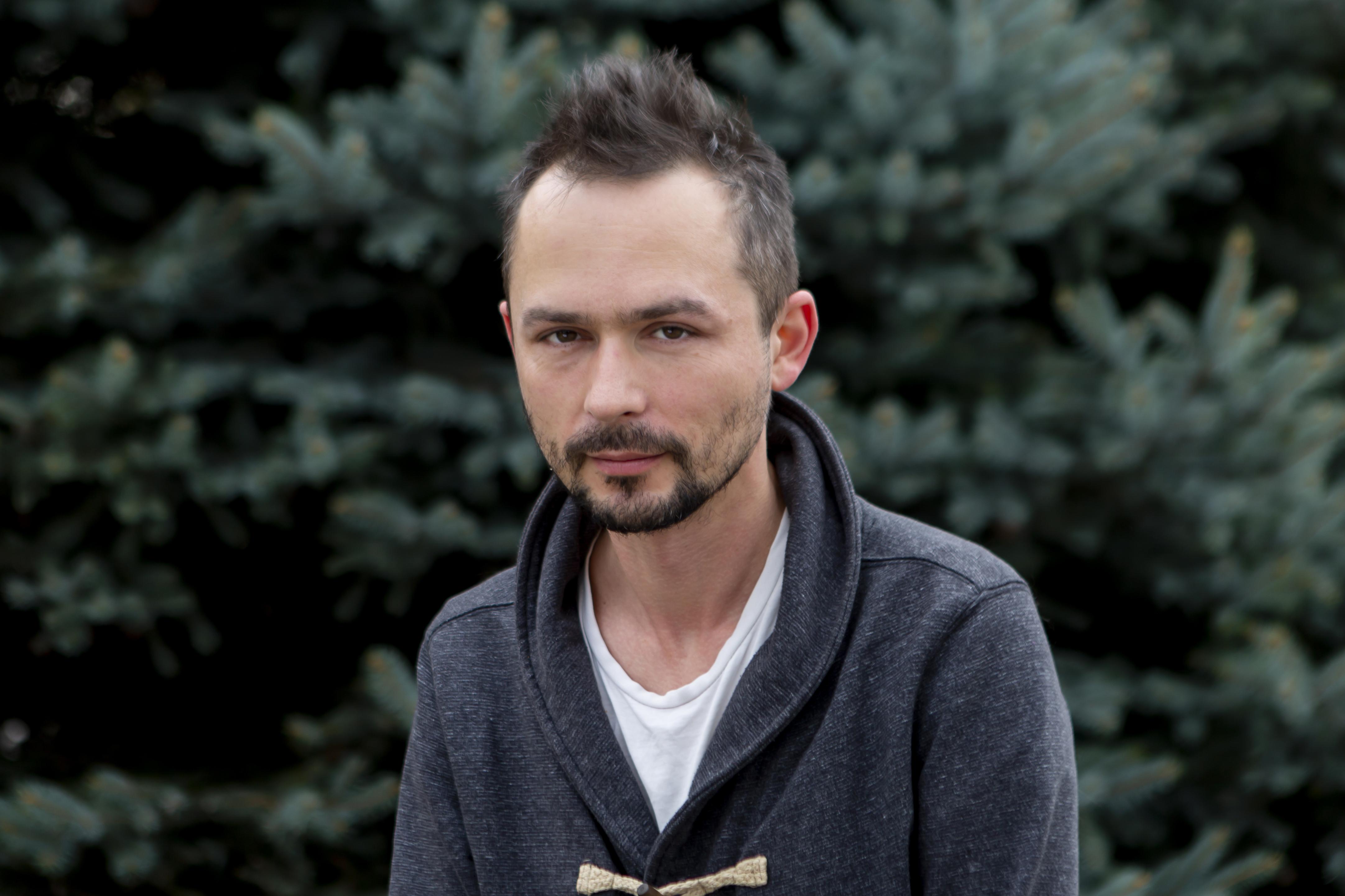 Zdjęcie przedstawia mężczyznę. Ma wąsy i niewielką brodę