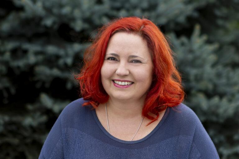 Zdjęcie przedstawia szeroko uśmiechniętą kobietę.