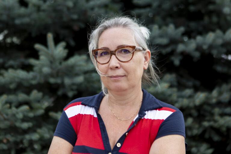 Zdjęcie przedstawia kobietę. Włosy ma zaczesana i upięte z tyłu. Ma okulary