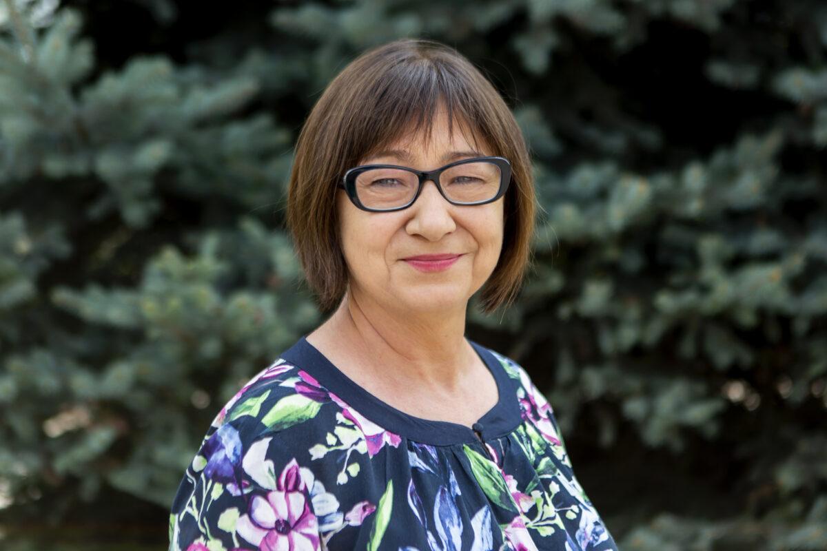 Zdjęcie przedstawia kobietę. Ma krótkie włosy i okulary.