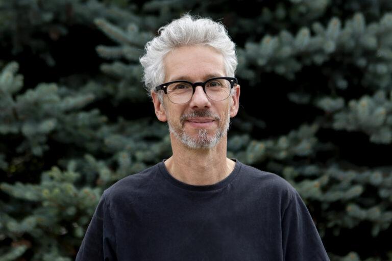 Zdjęcie przedstawia mężczyznę, ma krótkie kręcone włosy,brodę i okulary. Uśmiecha się.