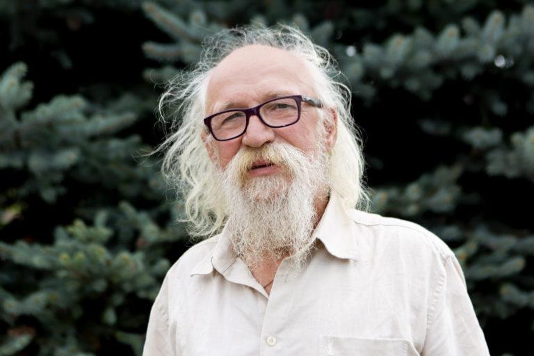 Zdjęcie przedstawia mężczyznę z dłuższymi włosami i brodą, w okularach.