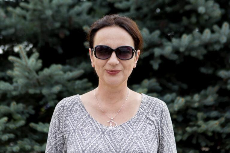 Zdjęcie przedstawia kobietę, ma ciemne okulary na nosie