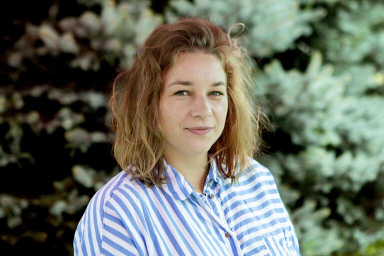 Zdjęcie przedstawia młodą kobietę. Ma włosy do ramion. Ubrana jest w koszulę w paski.