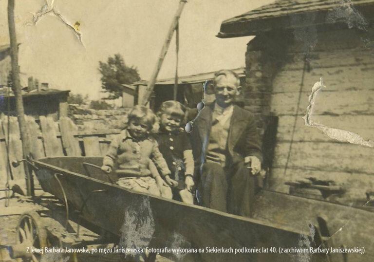 To jest bardzo stare zdjęcie, z pewnością pochodzi z wczesnych lat po II wojnie światowej. Przedstawia mężczyznę zdójkę dzieci siedziących na wozie. Za nimi widzimy fragment drewnianego domu.