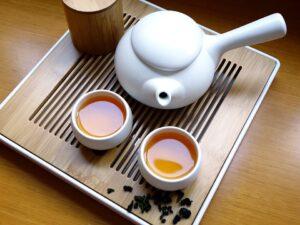 Na zdjęciu widzimy chiński czajniczek do parzenia herbaty oraz dwie filiżanki wypełnione herbatą. Stoją na tacy.