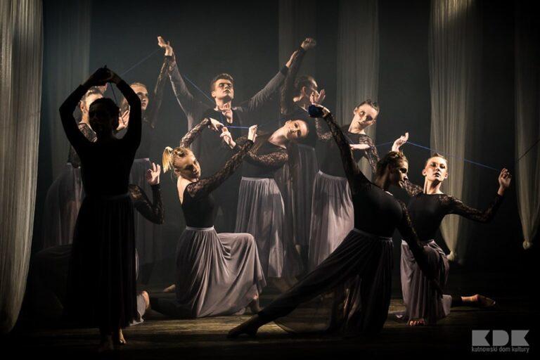 Zdjęcie przedstawia grupę młodych ludzi na scenie. Stoją w teatralnych pozach.