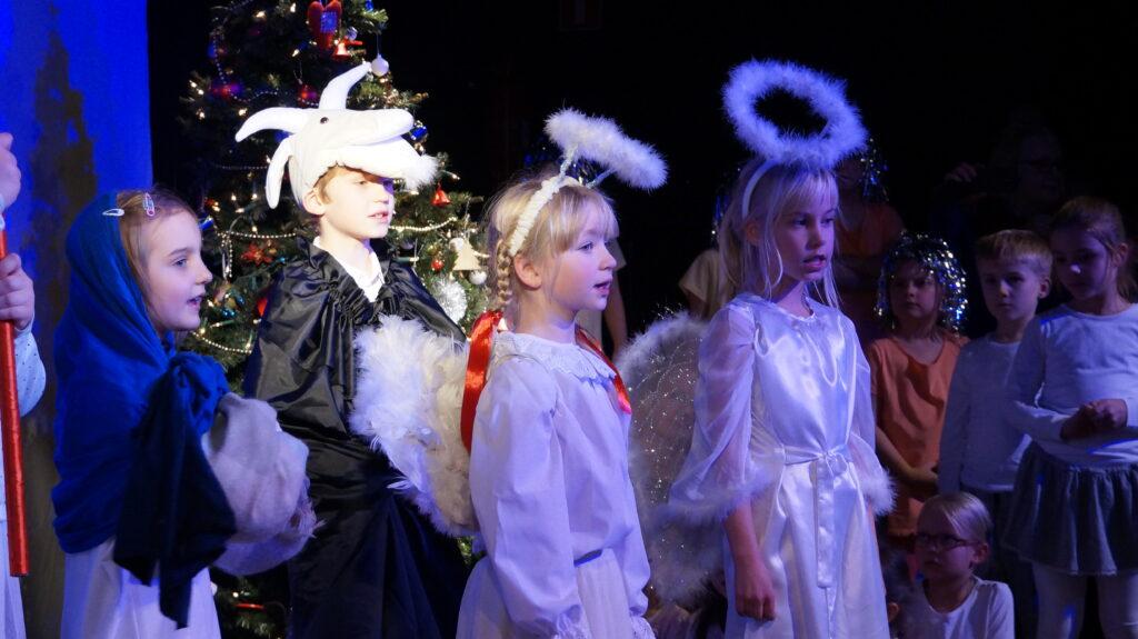Zdjęcie przedstawia dzieci na scenie ze spektaklu z okazji Świąt Bożego Narodzenia.