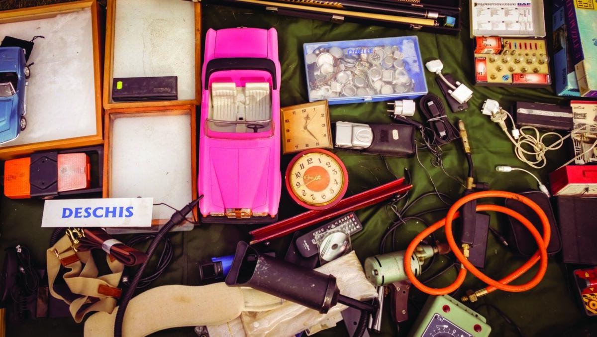 Przedmioty sfotografowane z góry. samochód zabawkę, zegarek, długopisy, wtyczki - wygląda to jak stoisko na pchlim targu