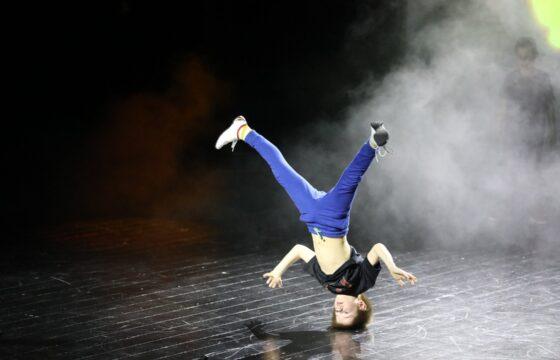 Breakdance - kilkuletni chłopiec stoi na głowie, w tle opary mgły