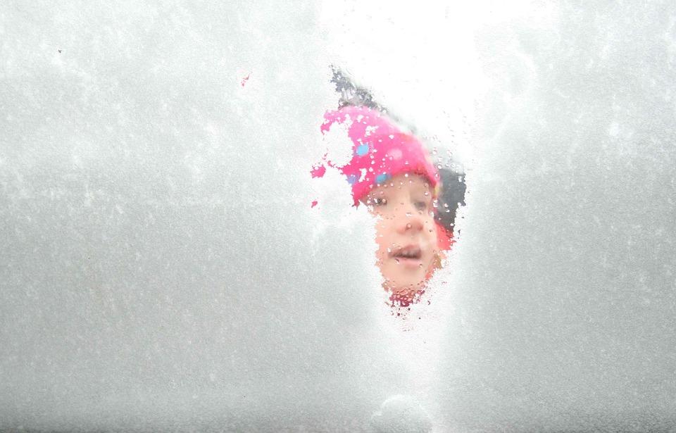 Zdjęcie przedstawia twarz dziewczynki zaglądającej przez zaśnieżone okno.