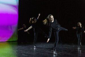Zdjęcie przedstawia 4 dziewczynki na scenie. Tańczą. Ubrane są w leginsy i podkoszulki