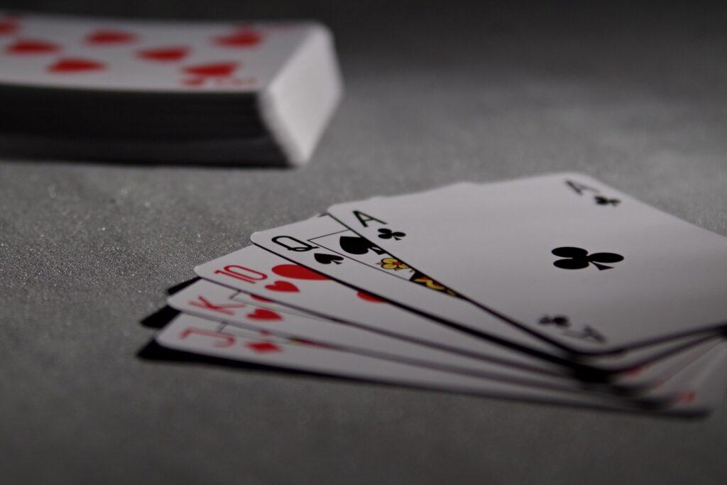 Zdjęcie przedstawia talię kart - część kart leży na kupce, część jest rozłożona w formie wachlarza.