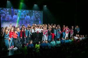 Zdjęcie przedstawia dużą grupę ludzi na scenie.
