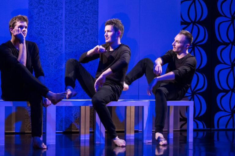 Trzech młodych mężczyzn na scenie, siedzą na stołkach, każdy w innej pozie