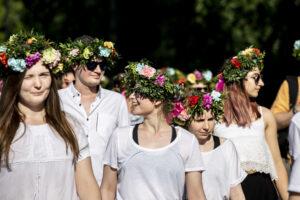 Grupa uśmiechniętych młodych ludzi, wszyscy mają na głowach wianki z żywych kwiatów.