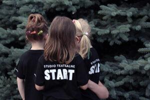 Zdjęcie przedstawia 3 dziewczynki. Stoją tyłem do obiektywu. Na koszulkach mają napis Start Studio Teatralne..