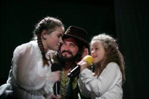 Na zdjęciu dwie dziewczynki, między nimi mężczyzna w kapeluszu. Dziewczynka z prawej trzyma w dłoni mikrofon.
