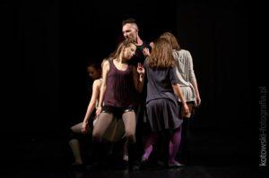 Scena, na niej tancerze, w środku chłopak, wokół niego dziewczyny.