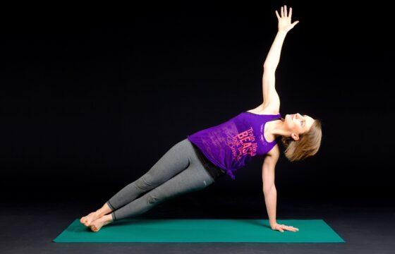 Kobieta w stroju do ćwiczeń na macie. Jedną ręką i stopami oparta jest na macie, druga ręka wyciągnięta w górę.