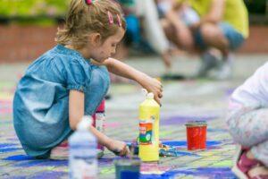 Kucająca dziewczynka maluje farbami.