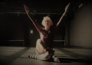 Kobieta siedzi podłodze z rękami wyciągniętymi w górę.