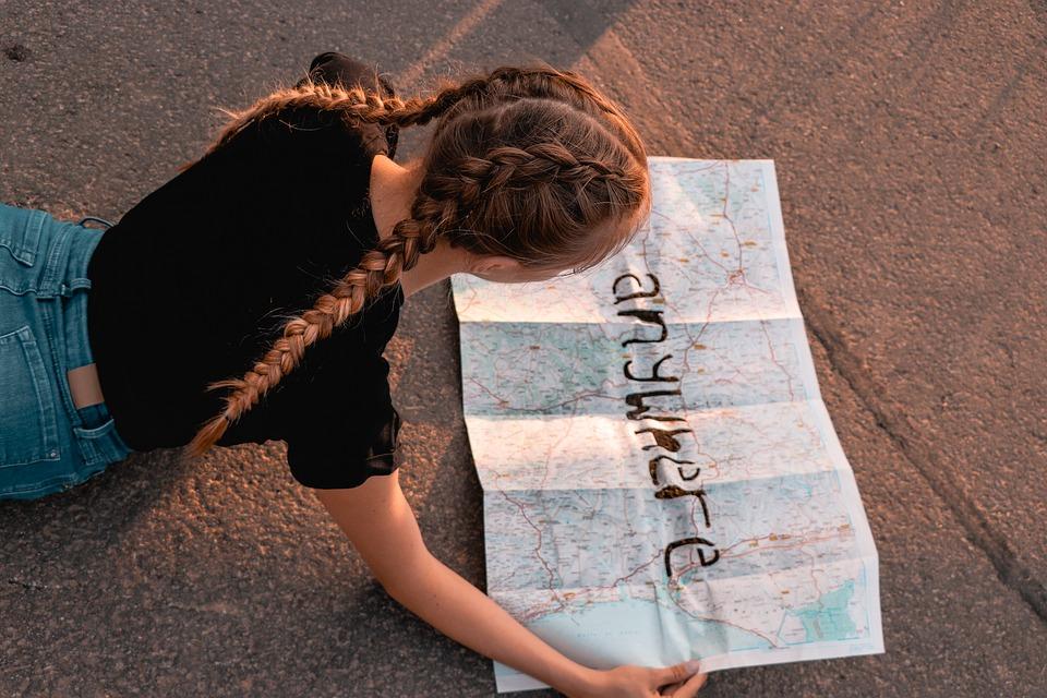 Dziewczyna pochyla się nad mapą.
