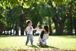 Kobieta przybija piątkę z kilkuletnim chłopcem. Są w parku.