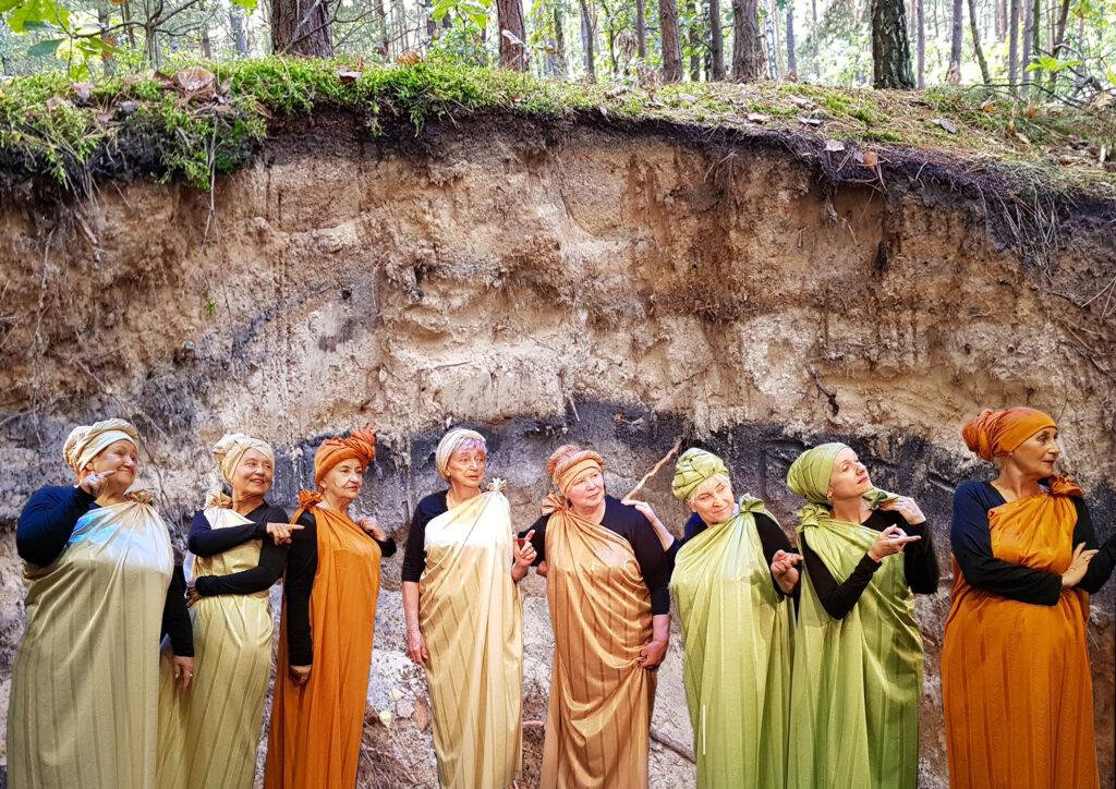 Osiem kobiet w starszym wieku pozuje do zdjęcia, ubrane są w jednym stylu, na głowach mają turbany.