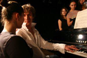 |Zdjęcie: scena, przy fortepianie siedzą chłopak i dziewczyna, za fortepianem grupa dziewczyn z wachlarzami w dłoniach
