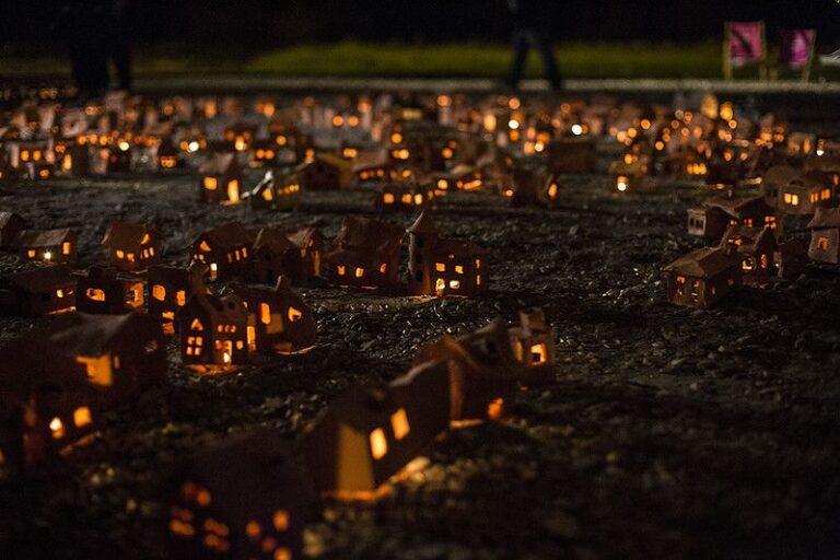 Zdjęcie: ustawione na ziemi małe gliniane domki, ze świeczkami wewnątrz.