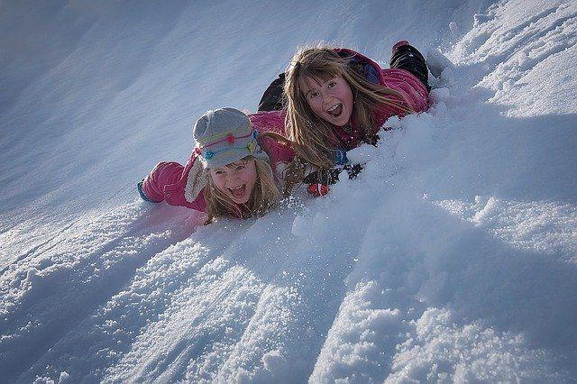 Zdjęcie, dwie dziewczynki leżą na brzuchach w śniegu