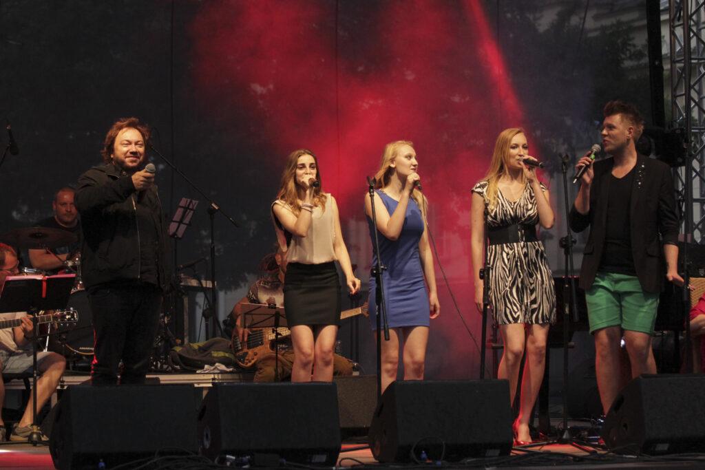 Zdjęcie - grupa młodych ludzi na scenie , wszyscy z mikrofonami w dłoniach.
