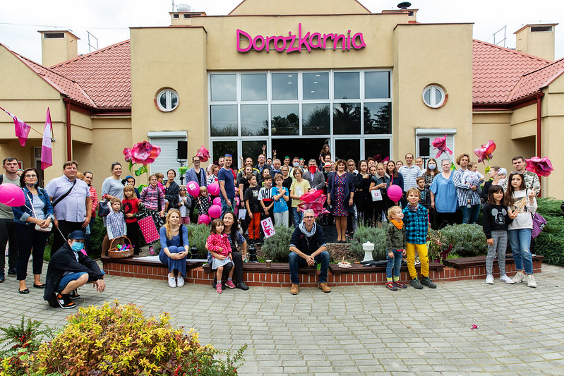Zdjęcie - duża grupa osób w różnym wieku pozuje do zdjęcia przed budynkiem z napisem Dorożkarnia
