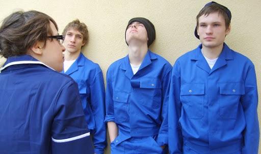 Zdjęcie - trzej chłopcy nastolatkowie stoją oparci o ścianę, przed nimi (tyłem do kadru) stoi dziewczyna.