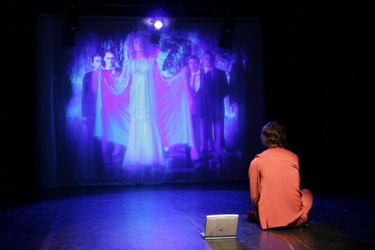 Zdjęcie - na scenie (tyłem do widowni) siedzi chłopiec, przed nim na dużym ekranie wyświetlany jest film. Obok chłopca leży ;a[top.