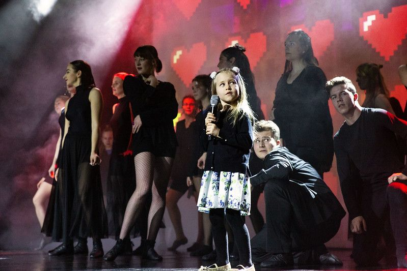 Zdjęcie sceny, na pierwszym planie kilkuletnia dziewczynka z mikrofonem, za nią grupa tancerzy
