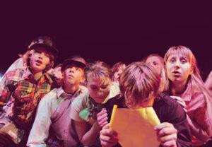 Grupa młodzieży na scenie, dziewczęta i chłopcy, stoją blisko siebie, ściśnięci. Chłopak nw pierwszym rzędzie patrzy na kartkę, którą trzyma w dłoniach blisko twarzy.