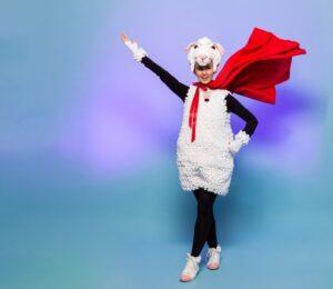 Kobieta w kostiumie owieczki, jedną rękę ma wyciągniętą w górę, druga spoczywa na boku. Na szyi powiewa duży szal.