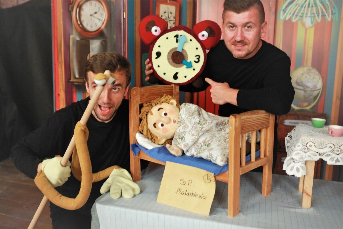 Zdjęcie ze spektaklu teatralnego dla dzieci. Na scenie dwóch mężczyzn i kukiełka