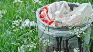 Kosz na śmieci stojący na bujnej trawie